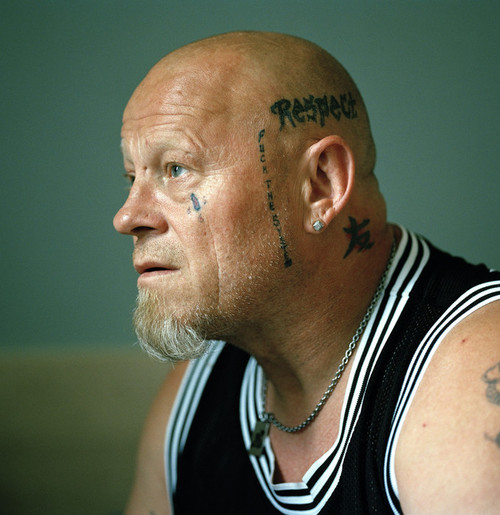 "Halden Prison, Norway, June 2014: In his late 40´s, inmate Tom has spent more of his adult life in prison than outside. Last time he was out he also had a serious motorcycle accident that almost killed him. In addition tho the tattoos on his left side, he also has ""F*** the Police inked on the right side of his skull. -- No commercial use -- Photo: Knut Egil Wang/Moment/INSTITUTE"