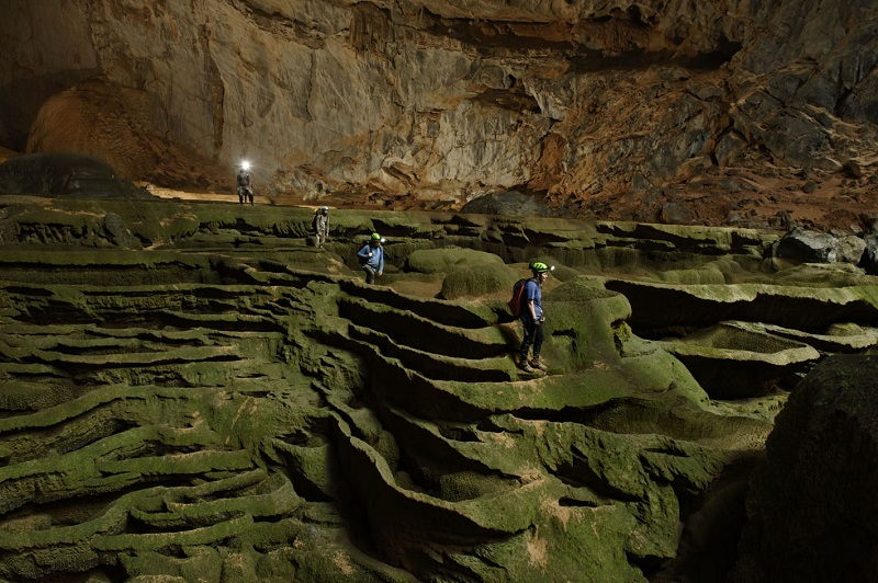 PIC FROM CARSTEN PETER/NATIONAL GEOGRAPHIC STOCK/CATERS NEWS - (PICTURED: Navigating an algae-skinned maze, expedition organizers Deb and Howard Limbert lead the way across a sculpted cavescape in Hang Son Doong) - These are the breathtaking images which capture the hidden depths of the worlds biggest cave passage - so large the end is yet to be found. Hidden in the depths of the Vietnamese jungle lies The Hang Son Doong, part of a network of over 150 caves. Discovered by British cavers in 2009, the cave passage in Phong Nha-Ke Bang National Park was originally thought to be a modest 150 metres long and 200 feet high. But these remarkable images - taken during two further expeditions of the caves - show the previously undiscovered depths of the magnificent cave passage, now the largest in the world. SEE CATERS COPY. DATE TAKEN: 2/05/2010 **FOR SALE IN UK, AUS, AU, BG, CA, CZ, SK, EG, ES, DE, IL, LT, NZ, RO, SA, ZA, CH, TR, UAE ONLY** **BYLINE IS MANDATORY, PLEASE USE AS ABOVE**