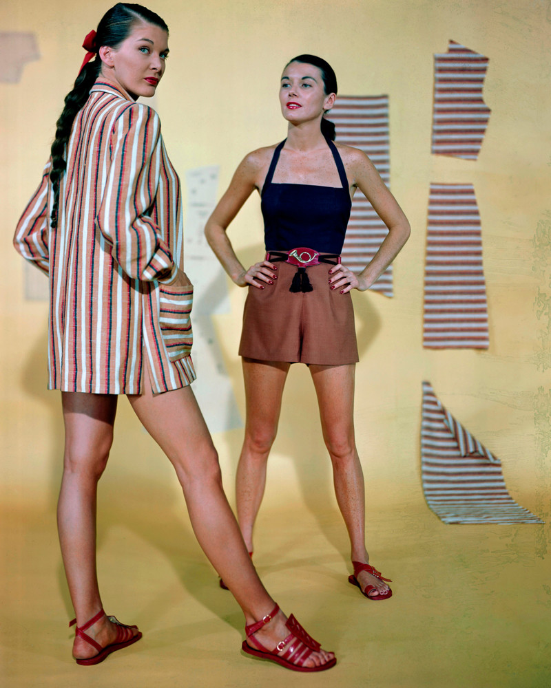 1947 --- Betty Bridges (left) models a Guatemalan cotton beach jacket, while Sabine shows off a beach playsuit with halter top. --- Image by © Genevieve Naylor/Corbis