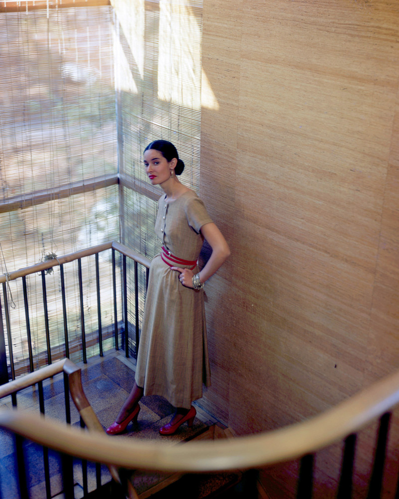 1948 --- A woman models a tan wool dress on a stairway. --- Image by © Genevieve Naylor/Corbis