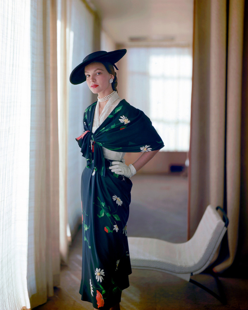 1952 --- A fashion model poses in a black floral summer dress and hat designed by Elsa Schiaparelli. --- Image by © Genevieve Naylor/Corbis