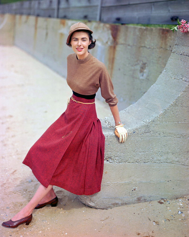 1949 --- A fashion model poses in a tweed skirt designed by M. Sloat, a sweater designed by Majestic, and a hat designed by Betmar. --- Image by © Genevieve Naylor/Corbis