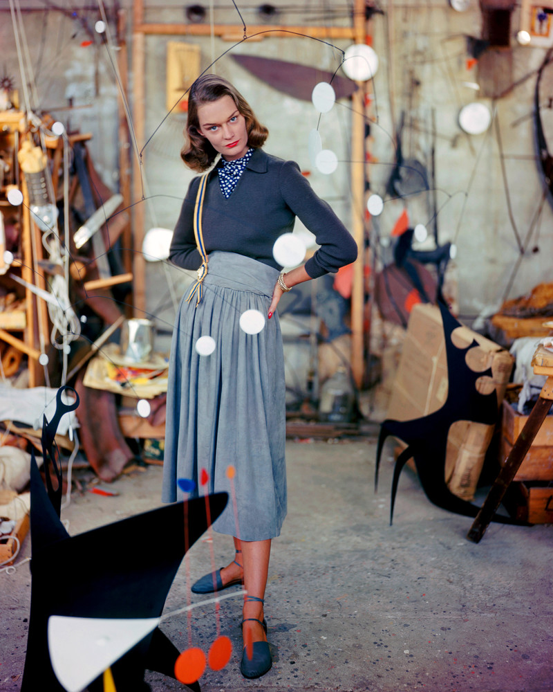 1948, Connecticut, USA --- A woman models a gray suede skirt in the studio of artist Alexander Calder, strolling among his mobiles. --- Image by © Genevieve Naylor/Corbis