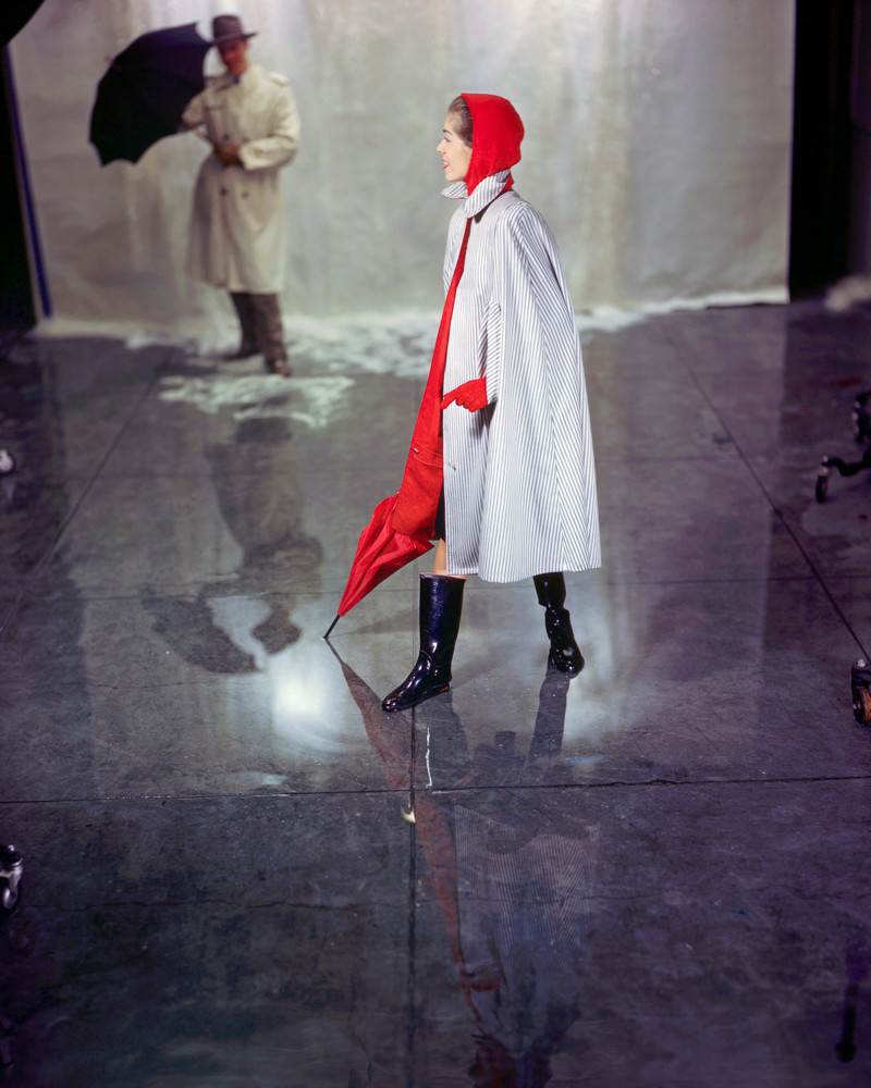 1949 --- A woman models a striped raincoat with a red hood and umbrella. A man wearing a trenchcoat stands behind her with an umbrella. --- Image by © Genevieve Naylor/Corbis