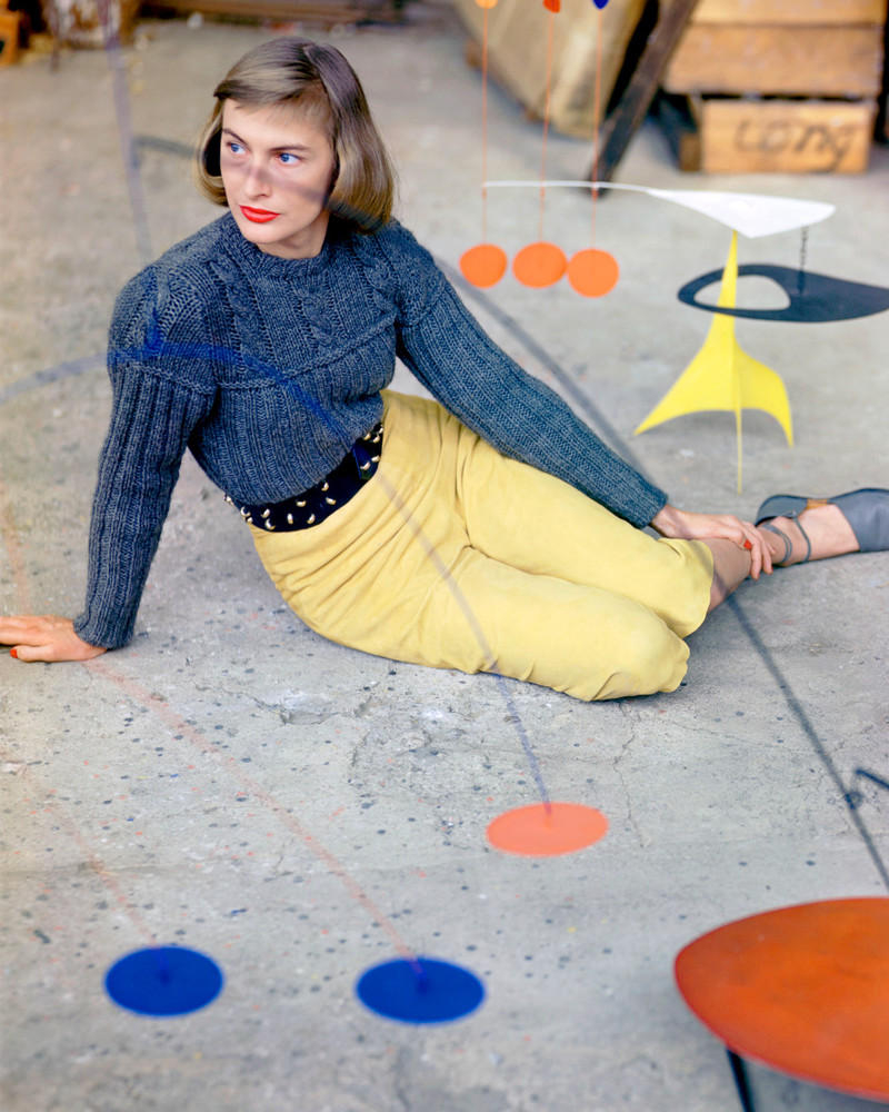 "1947, Connecticut, USA --- A fashion model poses in suede ""pedal pushers"" and a sweater behind one of Alexander Calder's mobiles at the artist's studio. --- Image by © Genevieve Naylor/Corbis"