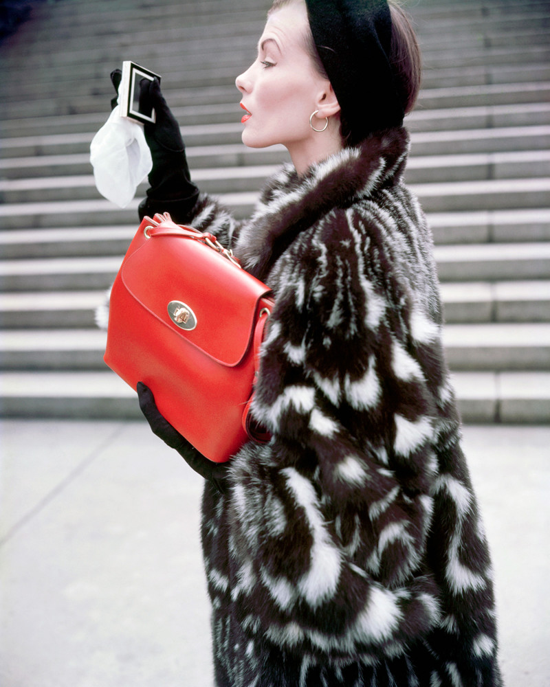 1949 --- A fashion model poses in a skunk fur jacket designed by Christian Dior and holds a red calfskin handbag. --- Image by © Genevieve Naylor/Corbis