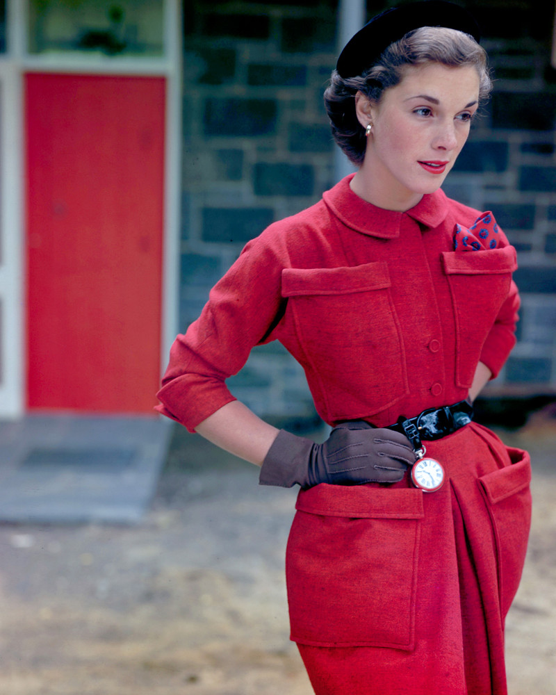 1949 --- A model poses in a tweed suit designed by Shelia Lynn and gloves designed by Shalimar. On the belt of the suit is a pocket watch designed by Otto Grun. --- Image by © Genevieve Naylor/Corbis