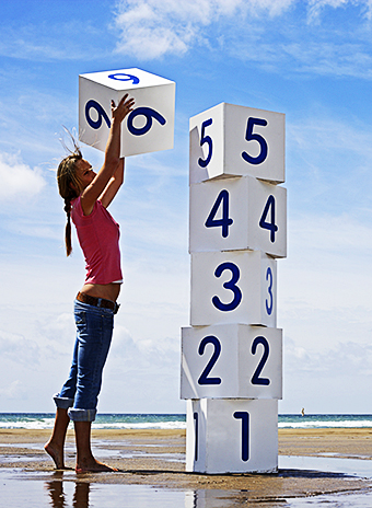 Woman on beach stacking white numbered boxes, side view