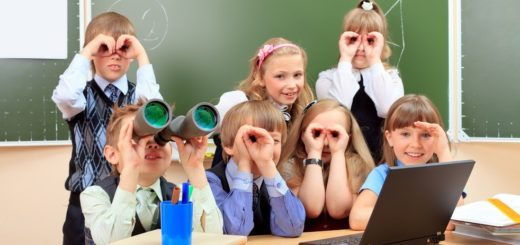 Happy schoolchildren at a classroom looking through binoculars. Education.